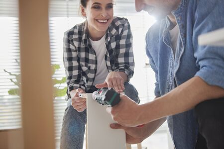 Couple cooperating in installing furnitures Stock Photo - 149638996