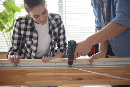 Woman helping her partner in furniture installing Stock Photo