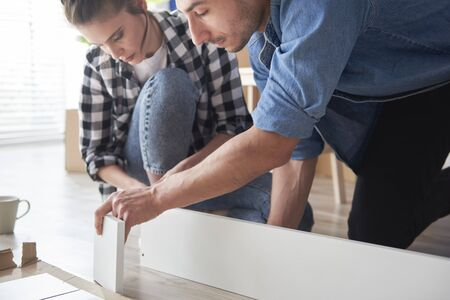 Serious couple installing new furnitures