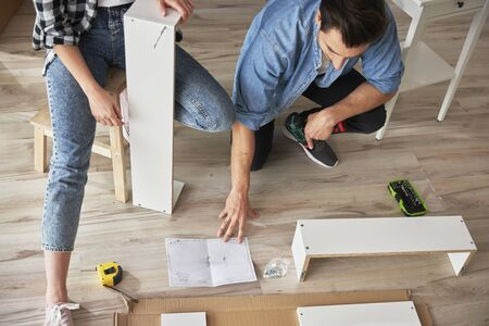 Top view of couple using paper manual during furniture installation