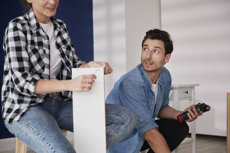 Young couple using  electric drill to install furnitures