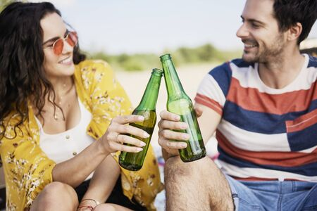 Young couple doing celebratory toast with beer bottles on beach