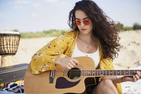 Smiling beautiful woman playing the guitar on the beach Stock Photo