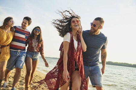 Happy friends walking on the beach.  Stock Photo