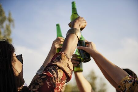 Group of people doing celebratory toast with beer bottles  Stock Photo