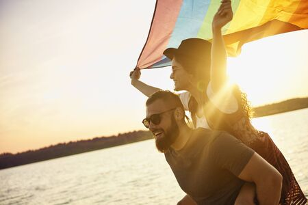 Happy man carrying woman with rainbow flag by sea
