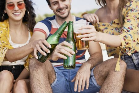 Group of friends doing celebratory toast with beer  Stock Photo