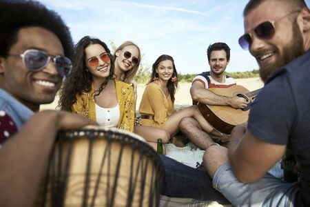 Portrait of happy friends sitting on beach with musical instruments Stock Photo