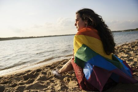 Girl sitting on the beach and watching sunset with rainbow flag