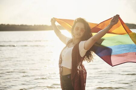 Beautiful young woman with rainbow flag at the beach