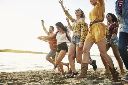 Happy friends running on beach at sunset Stock Photo - 149663089