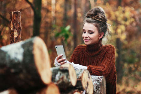 Woman in autumnal forest browsing a phone