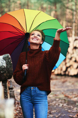 Woman with colorful umbrella catching rain