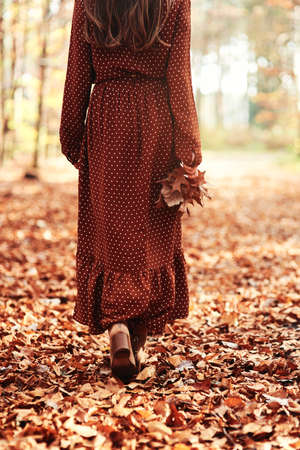 Woman walking away with an autumnal leaf