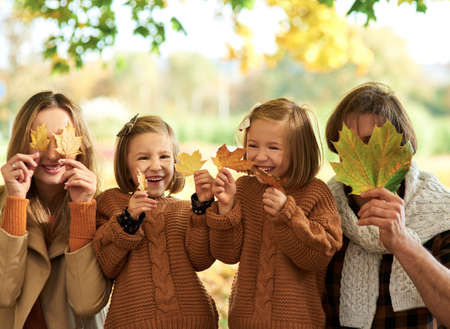Family picking leafs on the fall season