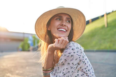 Happy young beautiful woman in a hat during the sunset