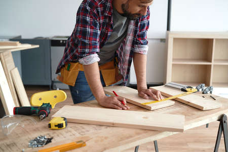 Carpenter measures the boards at the table