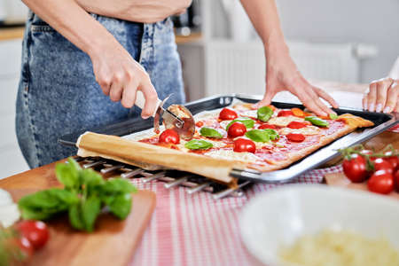 Close up of slicing homemade pizza on the table