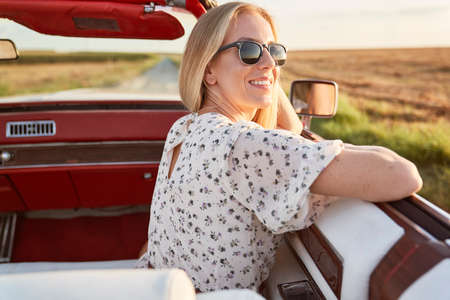 Happy beautiful woman sitting in the car