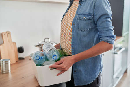 Woman segregating garbage in domestic kitchen