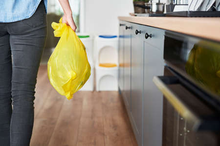 Woman carrying segregated plastic in yellow bag