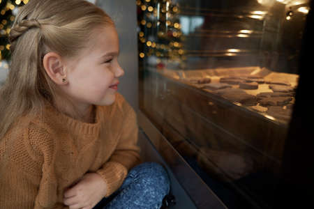 Little girl waiting next to oven for homemade cookies