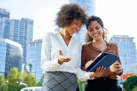Two businesswomen with digital tablet in the city