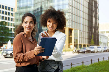 Two businesswomen with digital tablet outdoors