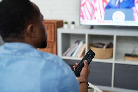 Rear view of black man watching TV Archivio Fotografico
