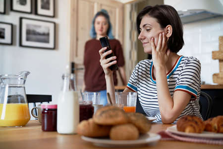 Smiling sending text messages during breakfast