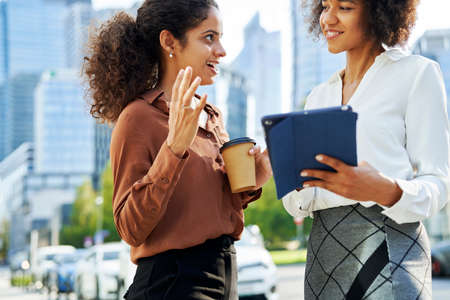 Two businesswomen discussing with digital tablet in the city