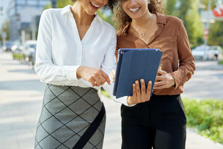 Two unrecognizable businesswomen using digital tablet in the city