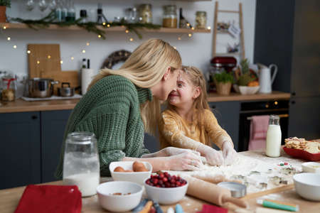 Mother and daughter lovingly in the kitchen while baking