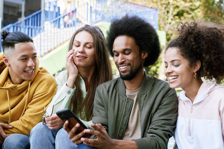 Group of friends sitting together with mobile phone