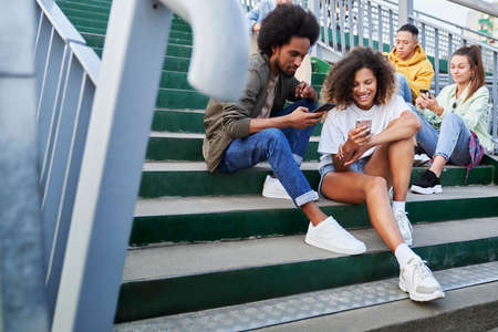 Group of young people sitting with your mobile phones outdoors