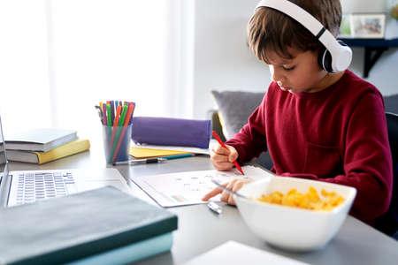 Boy doing homework during breakfast