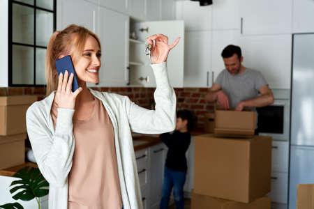 Happy woman calling and holding keys to a new house Foto de archivo