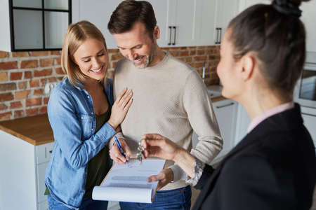 Couple with real estate agent signing contract of new apartment Foto de archivo - 166752067