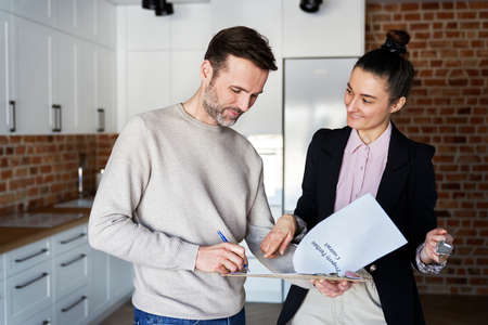 Man with real estate agent signing contract of new apartment