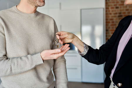 Close up of estate agent hands the keys to the man