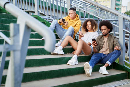 Three young people sitting on stairs with mobile phones Foto de archivo