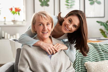 Portrait of adult daughter embracing her mother Foto de archivo
