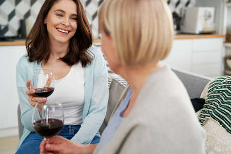 Two generation women drinking wine at home Foto de archivo