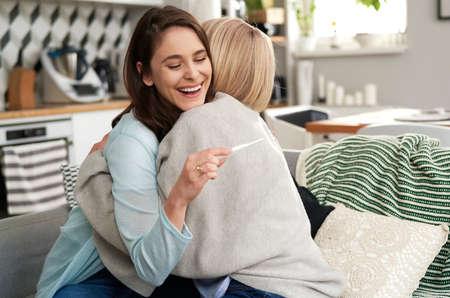 Senior woman congratulating daughter on positive pregnancy test