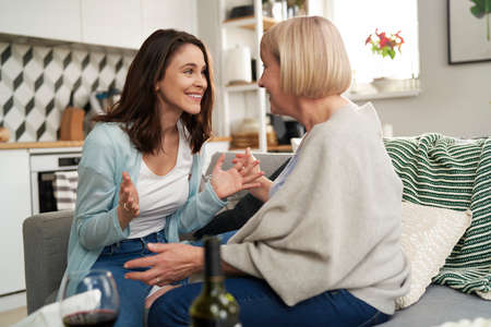 Happy woman communicates good news to her senior mother