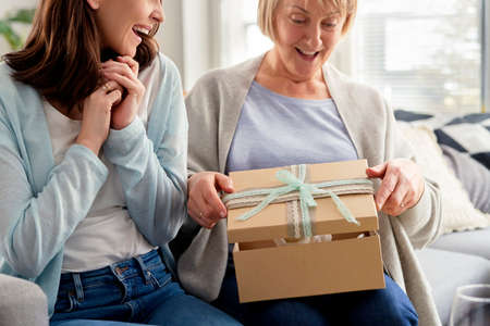 Excited adult daughter waiting for mom to open the gift