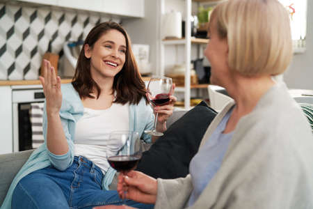 Two generation women spending time drinking wine at home