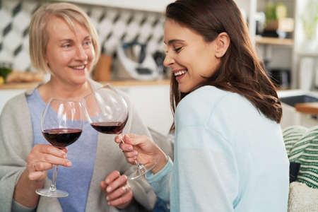 Happy adult daughter and senior mother toasting in wine