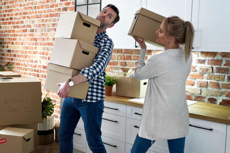 Couple during moving out takes cardboard boxes Foto de archivo