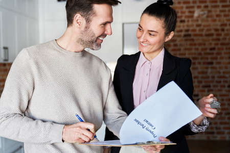 Happy man with estate agent signing contract of new apartment